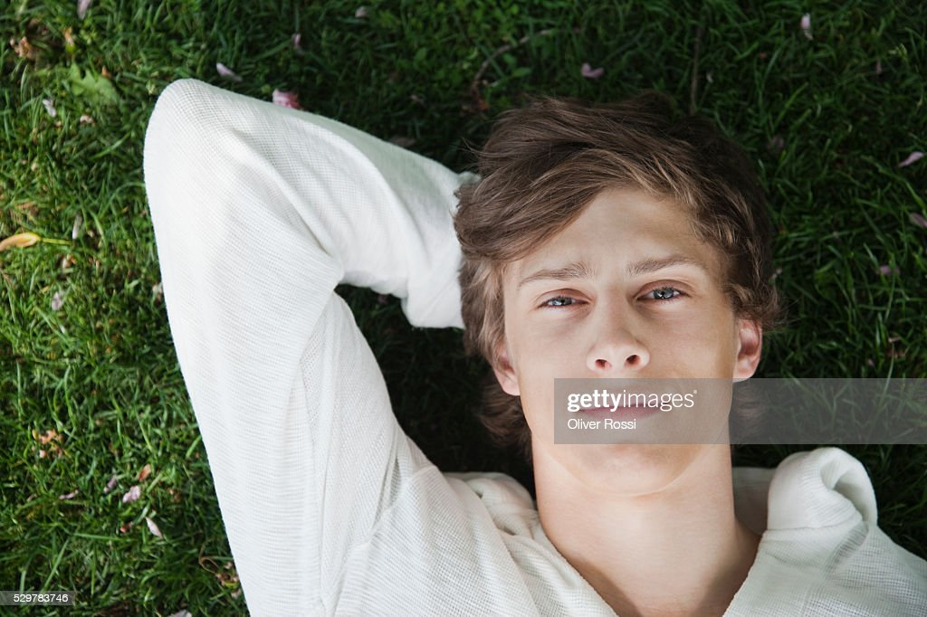 Young man lying in grass : Foto stock