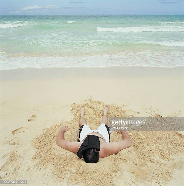 Young man lying in hole in sand on beach, elevated view