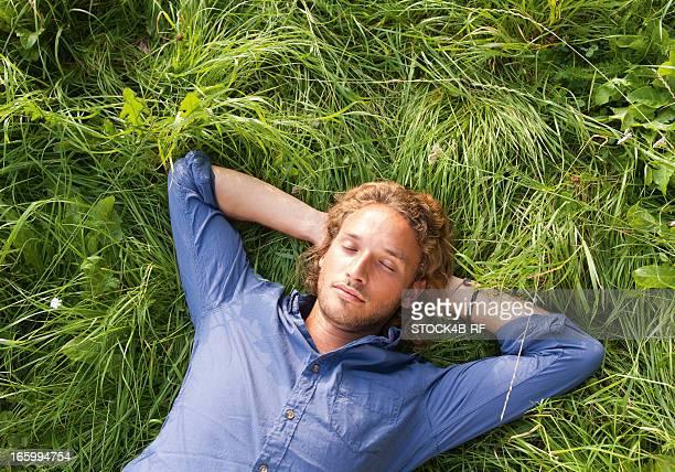 young man lying in meadow with eyes closed - liegen stock-fotos und bilder