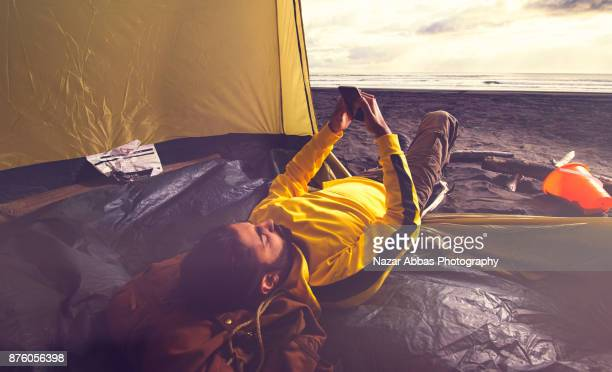Young man lying in tent at beach and using smart phone.