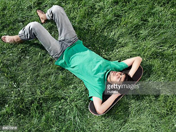 A young man lying in the grass with his head on a skateboard
