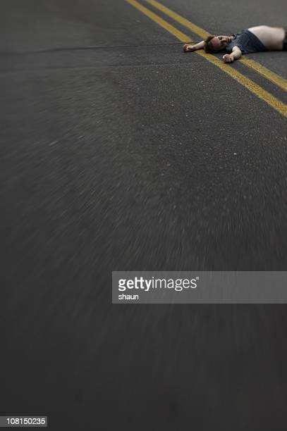 young man lying in the middle of road - dead bodies in car accident photos stock photos and pictures