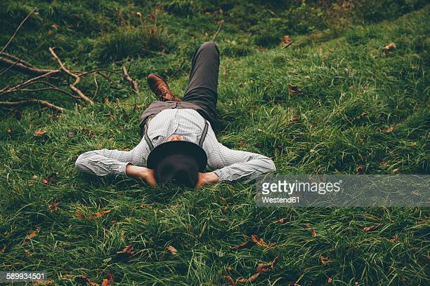 young man lying on a meadow with hands behind his head - legs behind head stock pictures, royalty-free photos & images