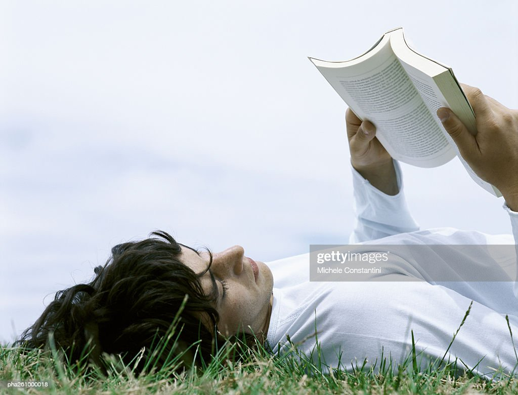Young man lying on back in grass reading book, head and shoulders : Stock Photo