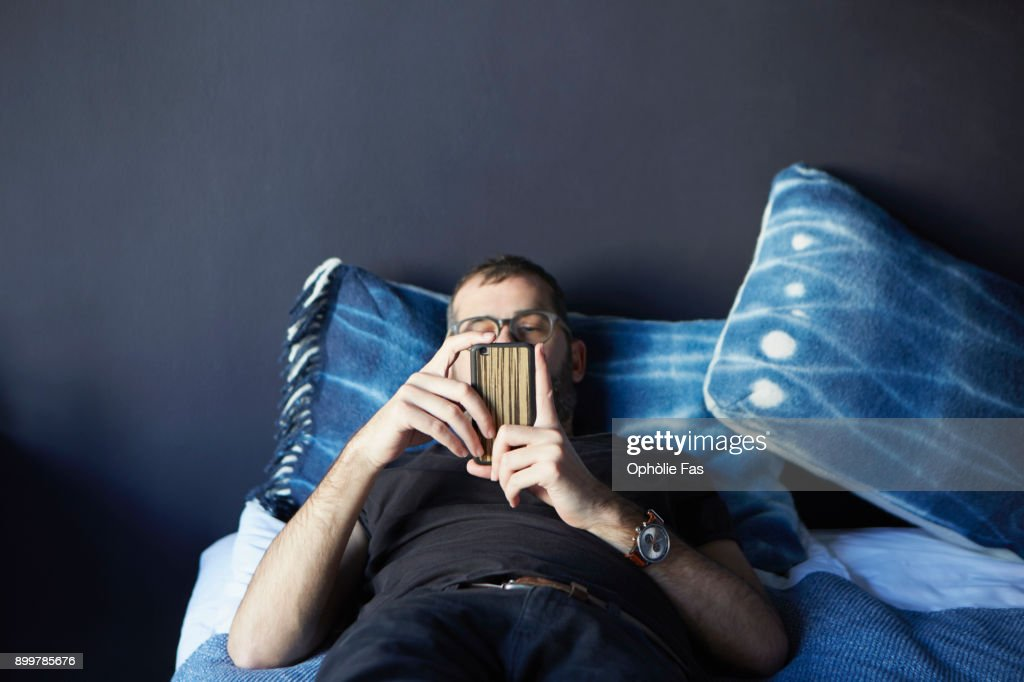 Young man lying on bed looking at smartphone : Stock Photo