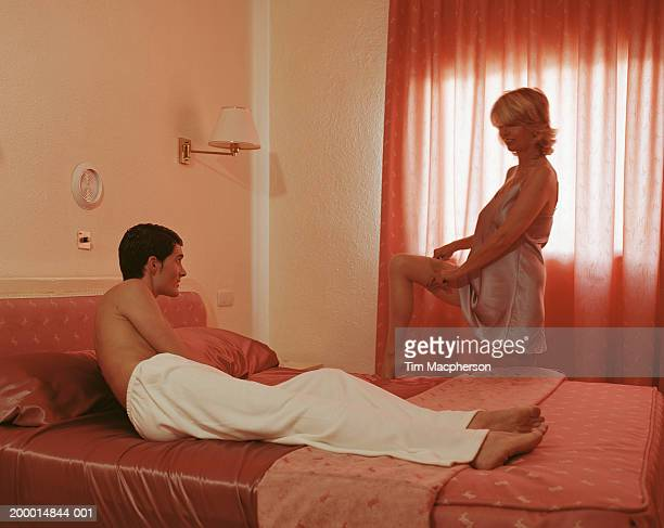 young man lying on bed, watching mature woman undress - gigolo photos et images de collection