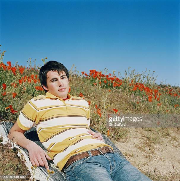 Young man lying on blanket in poppy field