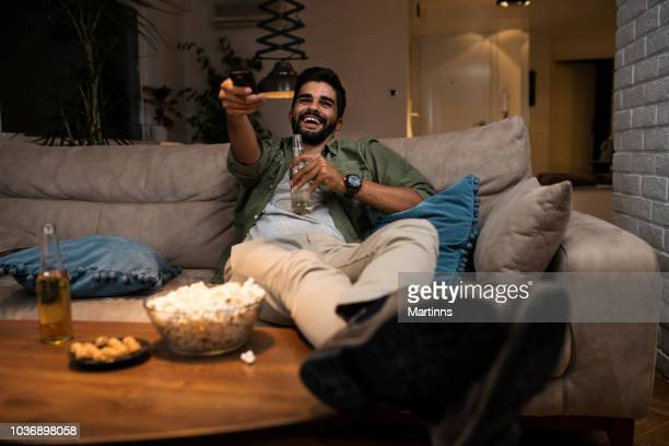 young man lying on couch watching tv - one man only stock pictures, royalty-free photos & images