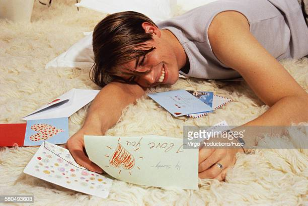 Young man lying on floor, reading love letter