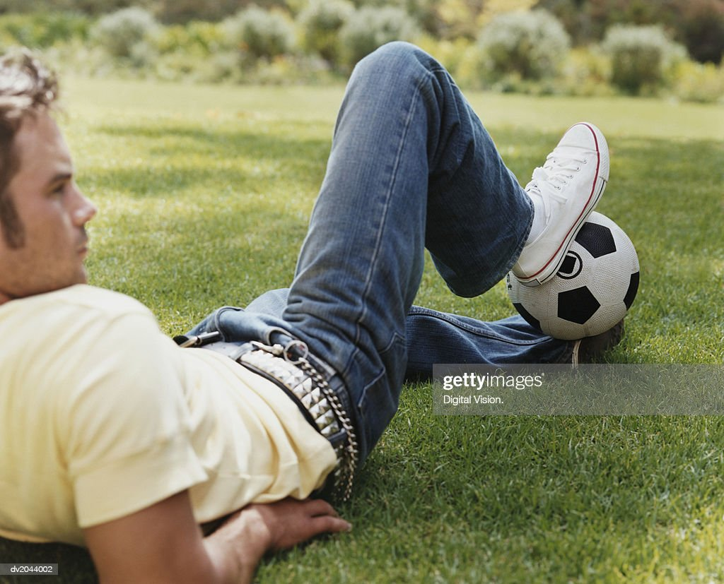 Young Man Lying on Grass Holding a Football Between His Feet : Stock Photo