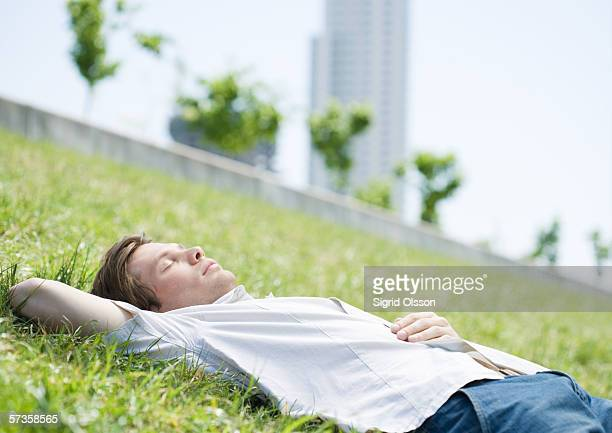 Young man lying on grass in urban park