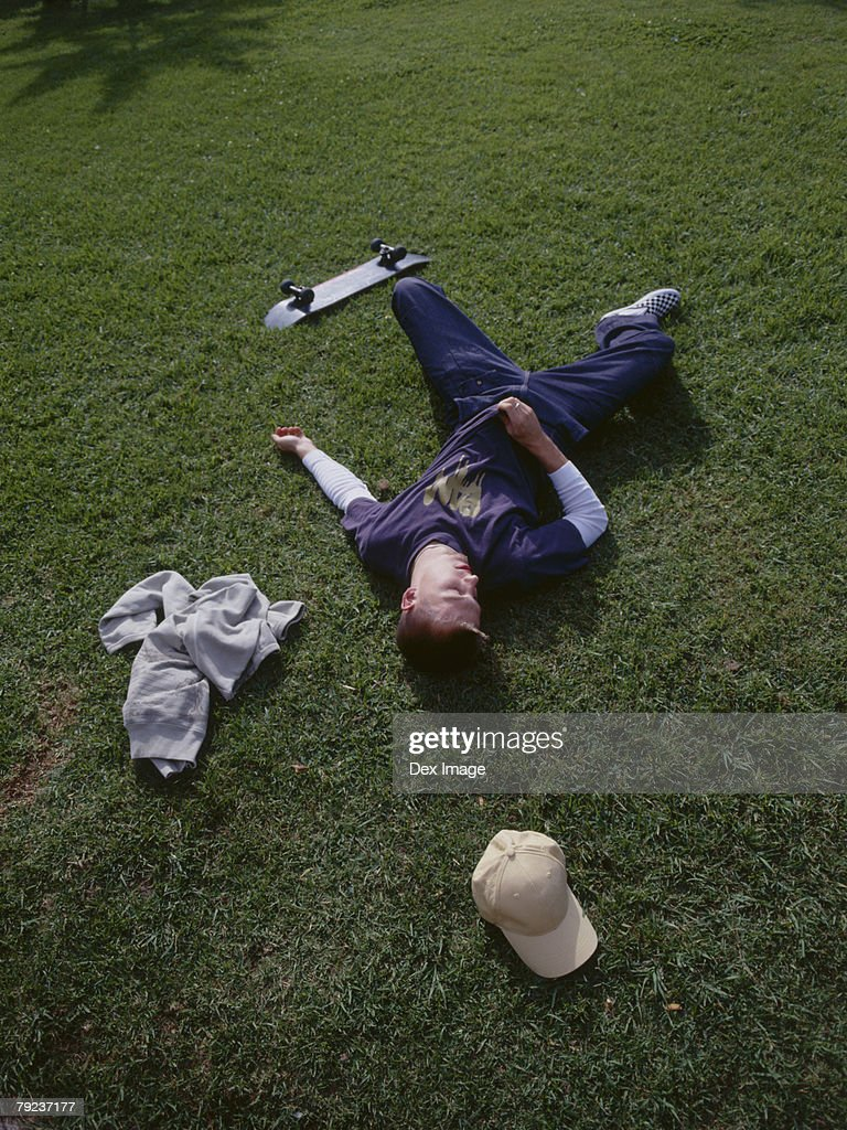 Young man lying on grass : Stock Photo