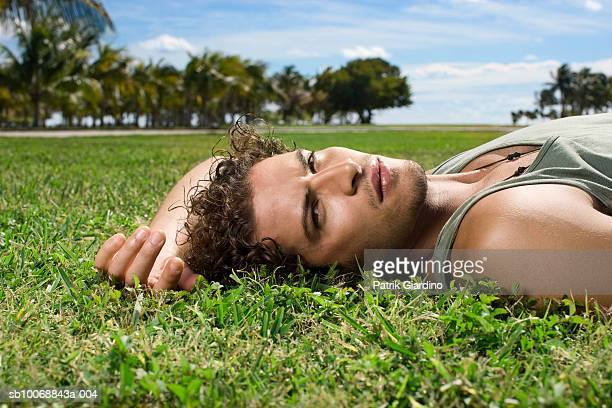 Young man lying on grass, portrait, close-up