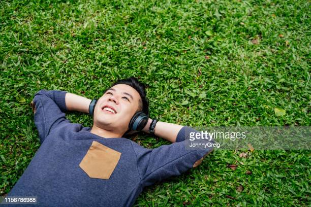 young man lying on grass wearing headphones - only young men stock pictures, royalty-free photos & images