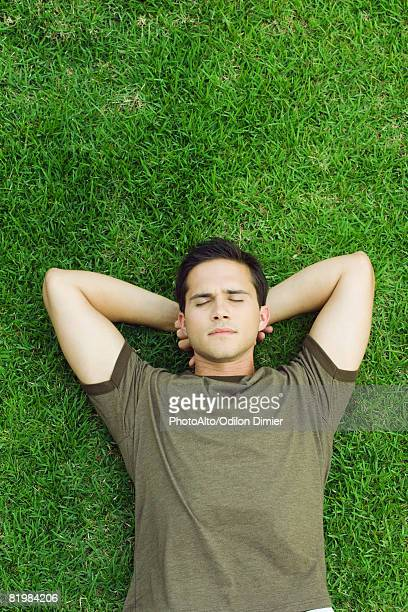 Young man lying on grass with hands behind head, eyes closed, high angle view