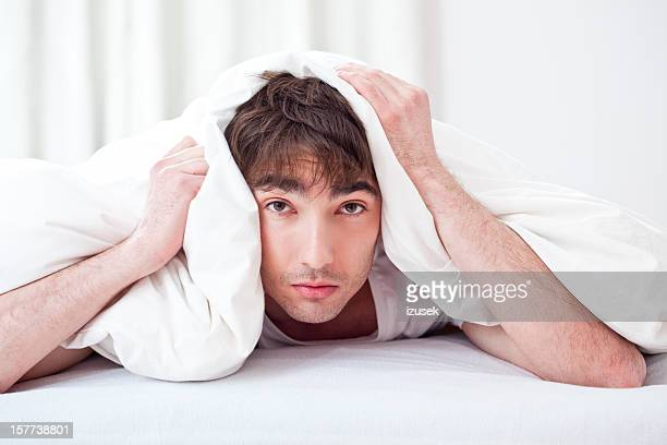 Young man lying on su el paladar con un duvet blanco