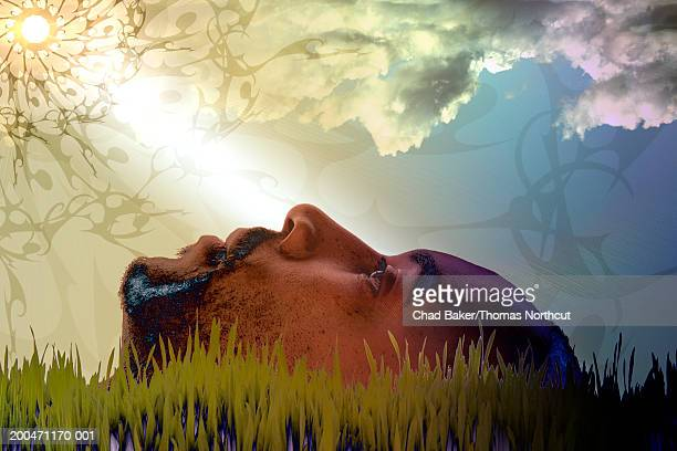 young man lying on lawn, side view (digital composite) - digital composite stock-fotos und bilder