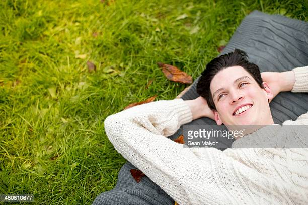 Young man lying on rug wearing sweater