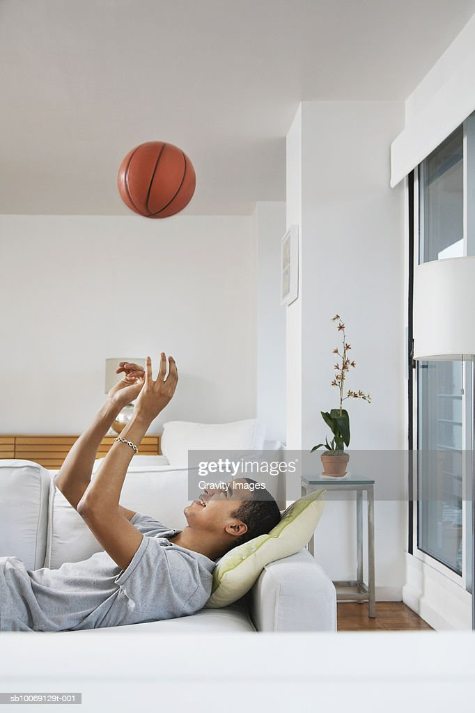Young man lying on sofa playing with ball, side view : Stockfoto