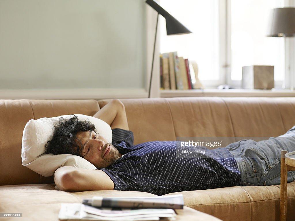 Young man lying on sofa watching TV : Stock Photo