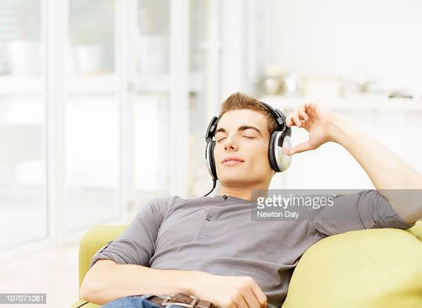 Young man lying on sofa, wearing headphones