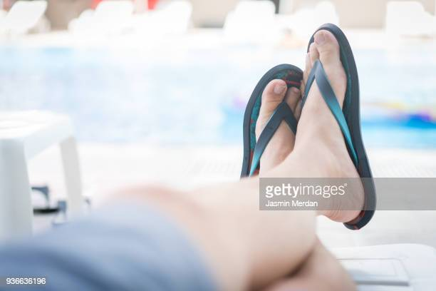young man lying on sun bed near pool - beau pied homme photos et images de collection