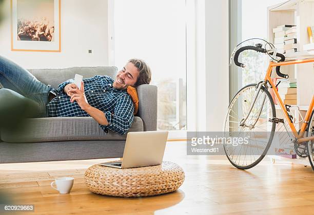 Young man lying on the couch at home looking at laptop