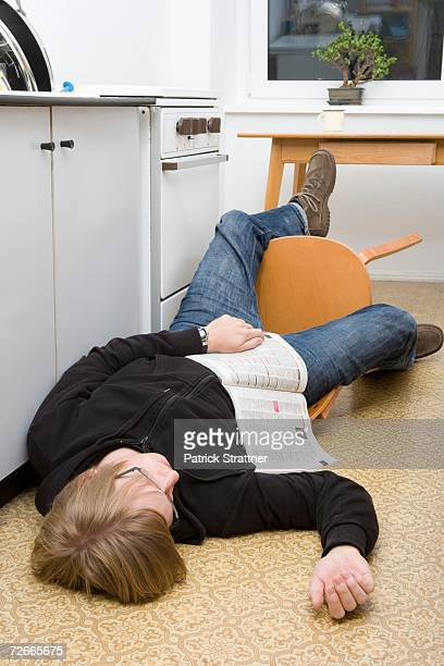 young man lying on the ground with magazine after falling back in a chair - lying down photos et images de collection