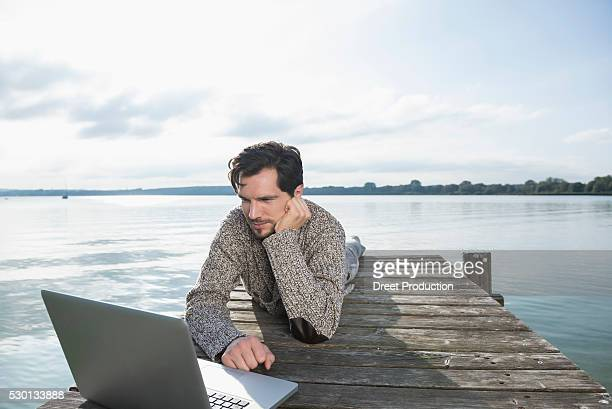 young man lying on wooden jetty lake laptop - pontoon bridge stock pictures, royalty-free photos & images