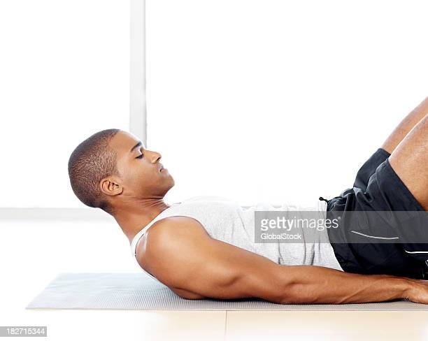 若い男性に横たわるヨガ用マットとエクササイズ