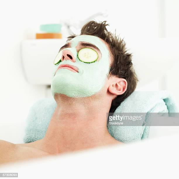 Young man lying with a face mask and cucumber slices on his face