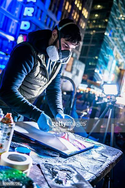 young man make aerography painting for public at time square - street artist stock photos and pictures