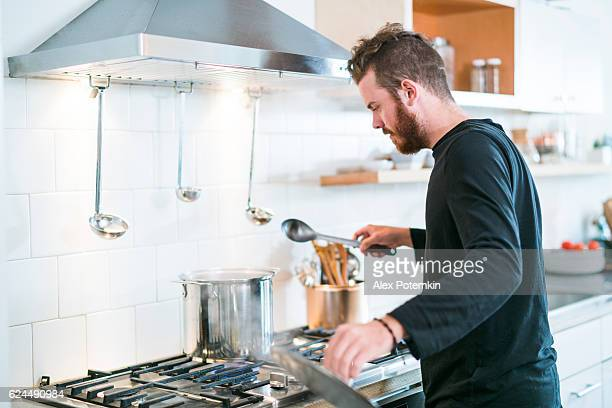 Young man make soup in kitchen