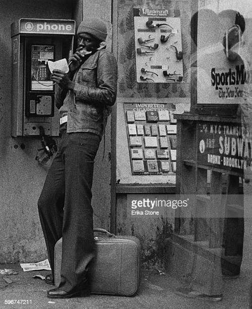 A young man makes a call on a payphone by a subway station near Times Square New York City circa 1975
