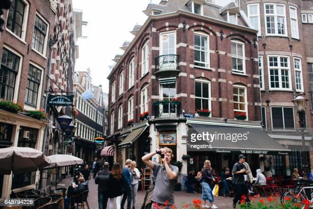 young man makes a photo in front of lunchroom de drie grafjes in amsterdam, netherlands - drie personen stock-fotos und bilder