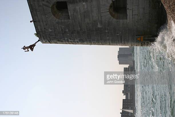 Young man makes a tombstone jump from the historic Round Tower at the entrance to Portsmouth Harbour.