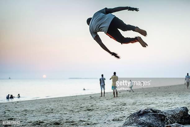 A young man makes an acrobatic trick on the local beach near the Stone Town in Zanzibar City Zanzibar Tanzania on 11 October 2016