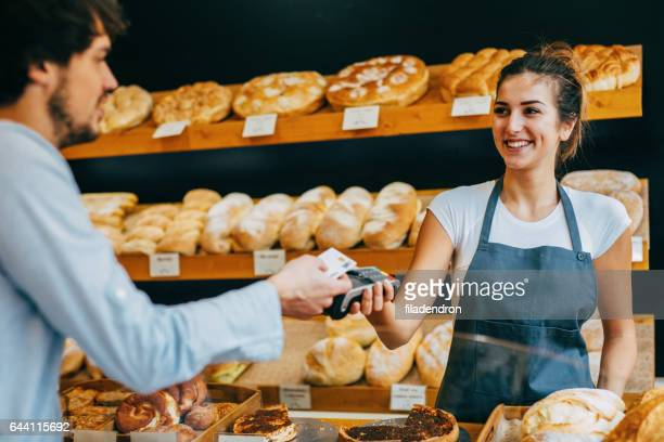 Young man making a contactless payment at a bakery