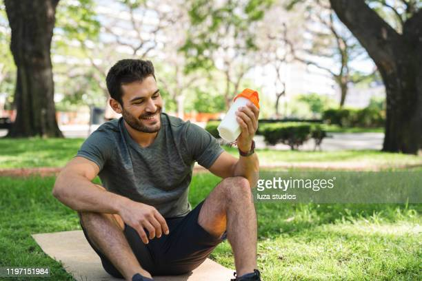 young man making a protein shake in the park - protein drink stock pictures, royalty-free photos & images