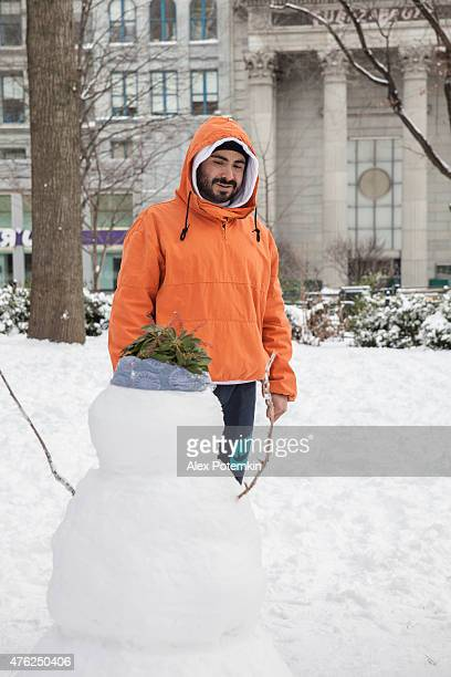 young man making a snowman - alex potemkin or krakozawr stock pictures, royalty-free photos & images