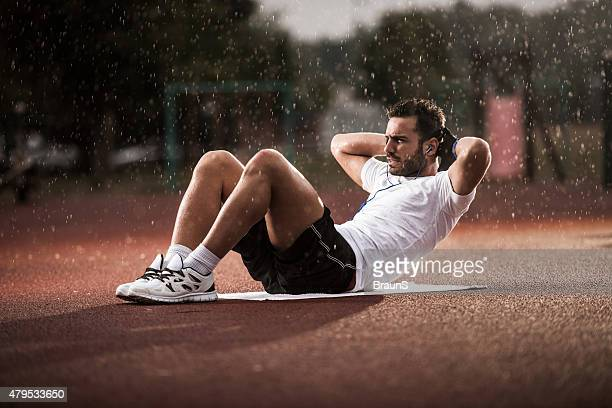 Young man making an effort while exercising sit-ups on rain.