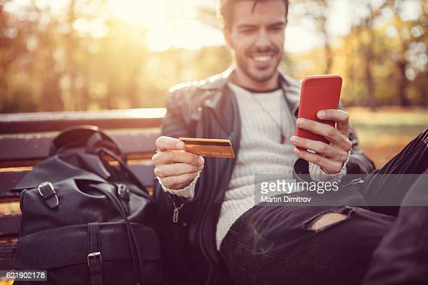 young man making credit card payment online - spending money stock pictures, royalty-free photos & images