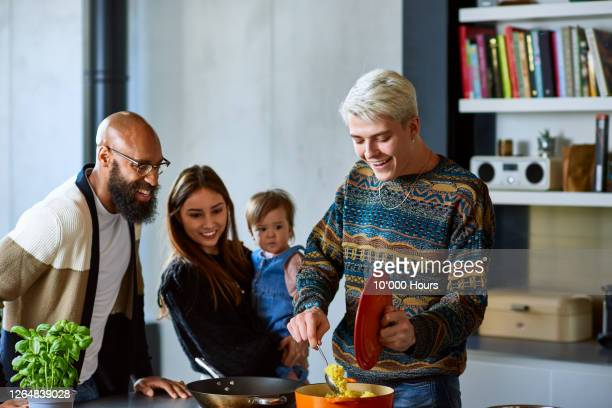 young man making food for multiracial family - cooking stock pictures, royalty-free photos & images