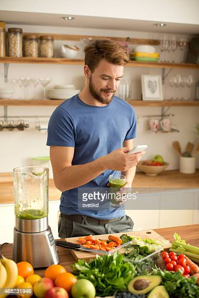 Young man making juice or smoothie in kitchen.