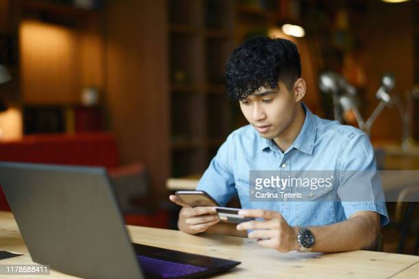 young man making payment on a phone app - customer engagement stock pictures, royalty-free photos & images