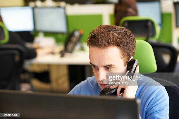 Young man making phone call in office