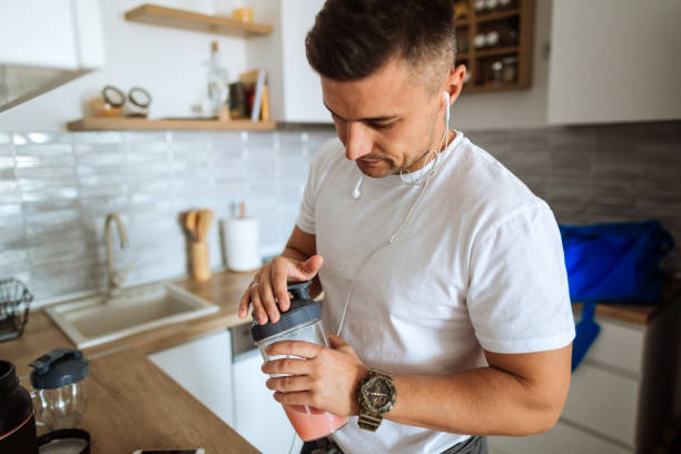 young man making protein shake before training - preparation stock pictures, royalty-free photos & images