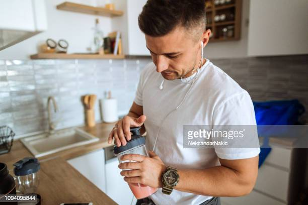 young man making protein shake before training - nutritional supplement stock pictures, royalty-free photos & images