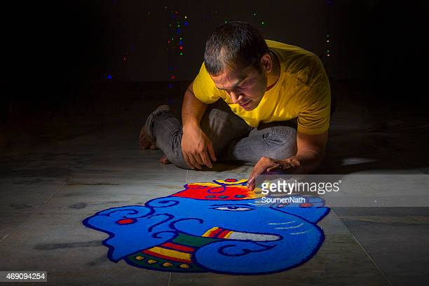 young man making rangoli on the occasion of diwali - rangoli stock pictures, royalty-free photos & images
