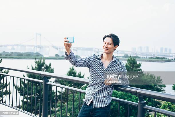 Young man making selfie with phone on street